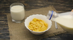 Fresh milk pouring into a bowl full of cornflakes in slowmotion Stock Footage