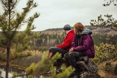Friends sitting on rock on remote hillside Stock Photos