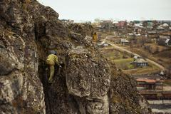 Hiker climbing rocky mountainside Stock Photos