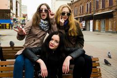 Caucasian women posing on bench Stock Photos