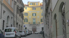Beautiful yellow building seen from a narrow street with parked cars in Trieste Stock Footage