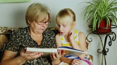 Grandmother reading a book for girls Stock Footage