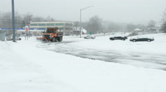 Orange city snow plow coming towards camera in a heavy snow storm Stock Footage