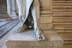 Close up of feet of carved statue on marble pedestal Stock Photos
