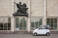 Compact car parked under sculpture on building Stock Photos