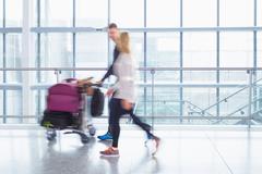Caucasian couple walking in airport Stock Photos