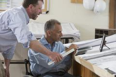 Caucasian architects talking in office - stock photo