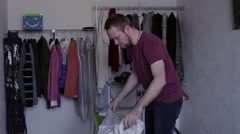 Man ironing a shirt with the help of an iron Stock Footage