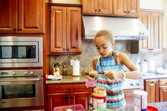 Mixed race girl scooping peanut butter in kitchen Stock Photos