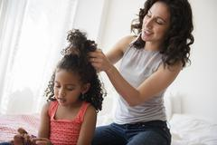 Mother styling hair of daughter - stock photo