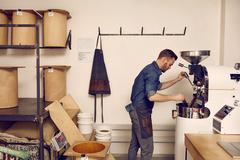 Business owner operating a modern coffee bean roasting machine Stock Photos