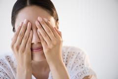 Hispanic woman covering her eyes Stock Photos