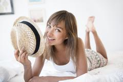 Mixed race woman with straw hat on bed Stock Photos