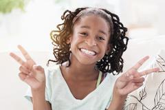 Smiling Black girl making peace sign Stock Photos