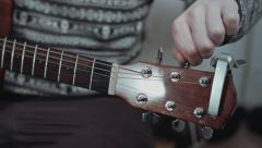 Close up of guitarist hand tuning acoustic guitar. Professional guitar player - stock footage