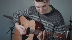 Professional guitarist player with acoustic guitar sitting and playing  - stock footage