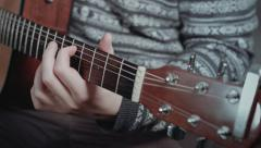 Close up of guitarist hand tuning acoustic guitar - stock footage