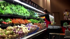 Worker arranging vegetables for sale in grocery store at produce department Stock Footage