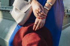 Caucasian woman holding hat and purse Stock Photos