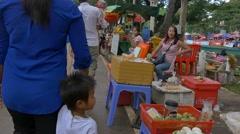 SIEM REAP, CAMBODIA - NOV 2015: Mother & son walking in market Stock Footage