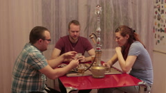 Three friends smoking shisha and playing cards Stock Footage