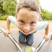 Caucasian boy playing on merry-go-round - stock photo