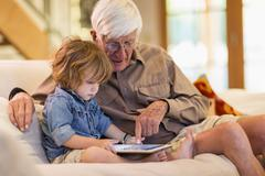 Caucasian grandfather and grandson using digital tablet Stock Photos