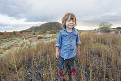 Caucasian boy smiling on rural hillside - stock photo