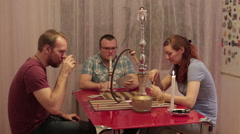 Women and men smoking shisha and playing cards Stock Footage