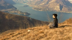Boy practicing meditation in the mountains at sunset Stock Footage