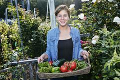 Mixed race woman holding basket of vegetables in garden Kuvituskuvat