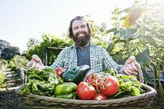 Caucasian man holding basket of vegetables in garden Kuvituskuvat