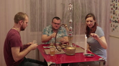 Friends fun with a hookah and playing cards Stock Footage