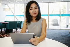 Japanese businesswoman using digital tablet in office - stock photo