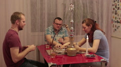 Men with woman smoking shisha and drinking alcohol - stock footage