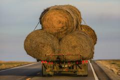 Truck carrying hay bales on rural highway - stock photo