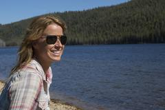 Caucasian woman sitting at remote river Stock Photos