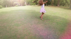 Young woman spinning and dancing in the park. Lens flares. Aerial video. Stock Footage