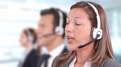 Call center phone operators working, talking, smiling and looking at the camera. Stock Footage
