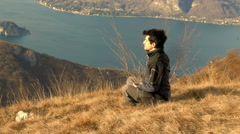 European boy meditates in front of a splendid panorama Stock Footage