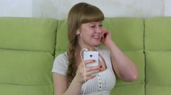 Young girl sitting on the sofa with smartphone and listening to music Stock Footage