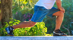 Closeup Man Does Morning Exercises Squats on Knee in Park Stock Footage