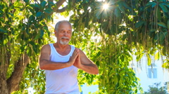 Closeup Old Man Does Yoga in Park Stock Footage