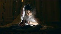 Girl reading book with a flashlight under the covers at night Stock Footage