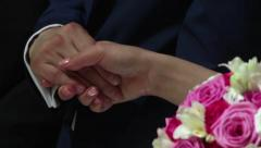 Bride and groom hold hands during the religious service 1 Stock Footage
