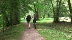 Girl and a boy walking in an alley in the park. Boy ride a bike, and get off Stock Footage