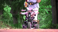 Grandmother walking her niece with a tricycle in park 01 Stock Footage