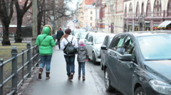 Two women with child walking on the city sidewalk along parked cars, rear view Stock Footage