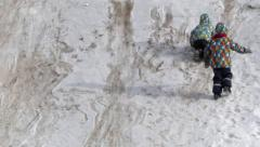 Funny action. Two children can't climb a snowy hill. Stock Footage