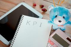 KPI list notebook with tablet calculator pencil on wood floor , digital effec - stock photo